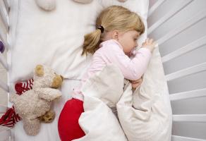 на картинке ребенок спит в кроватке.